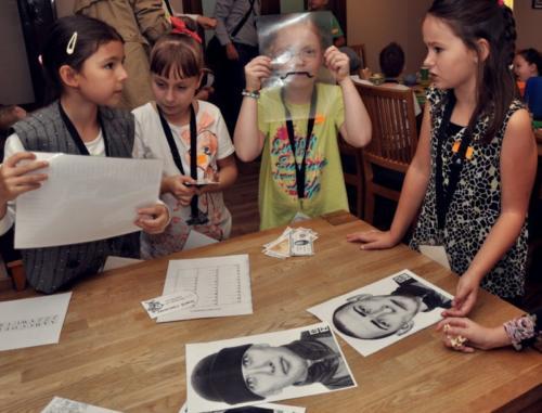 Zdjęcie przedstawia dzieci rozwiązujące zagadkę podczas urodzin w konwencji detektywistycznej w Family Park.