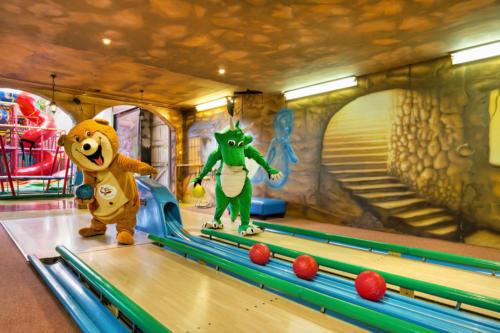 Na zdjęciu widać maskotki Smoka Fampo oraz Misia Bobusia grających w kręgle na kręgielni Centrum Zabaw Rodzinnych Family Park w Bydgoszczy. Postacie stoją.