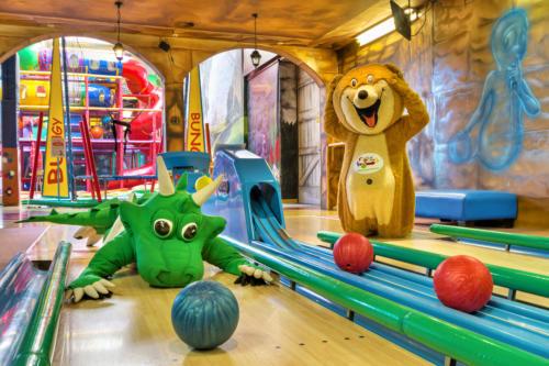 Na zdjęciu widać maskotki Smoka Fampo oraz Misia Bobusia grających w kręgle na kręgielni Centrum Zabaw Rodzinnych Family Park w Bydgoszczy. Postać smoka leży na torze do kręgli.