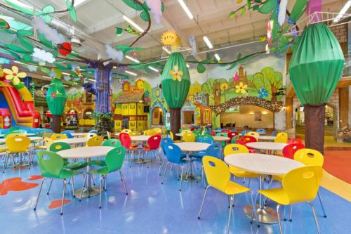 Zdjęcie ukazujące centralny punkt sali zabaw Family Park. Na pierwszym planie stoliki dla rodziców, w tle widać atrakcje: dmuchaną zjeżdżalnię oraz żółty domek, a także oddzielony akustycznie pokój ciszy dla rodziców z widokiem na salę.