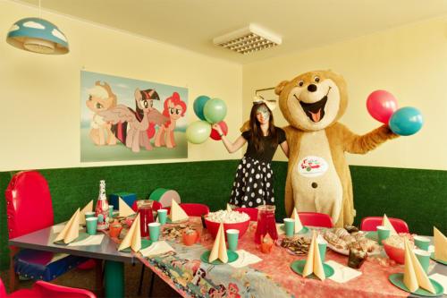 Na zdjęciu przebrana animatorka i maskotka Misia Bobusia prezentują bajkowy pokój urodzinowy w wystroju kucyki pony.