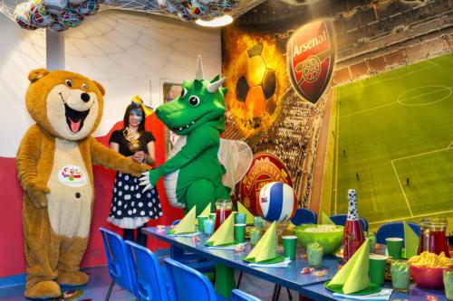 Miś Bobuś i Smok Fampo wraz z animatorką trzymają puchar w pokoju sportowym.