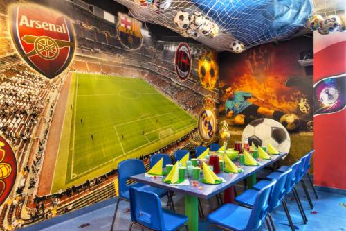 Stół i wystrój sportowego pokoju urodzinowego w Family Park. Na ilustracji ściennej dostrzec można motywy piłkarskie - stadion oraz herby klubów.