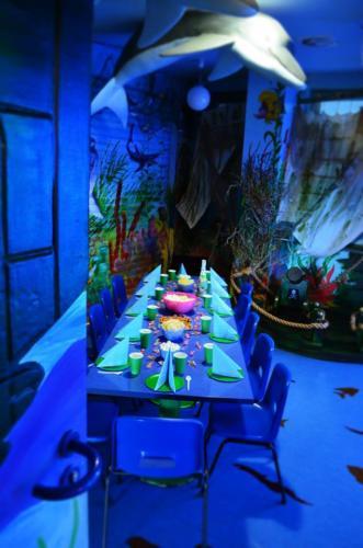 Zdjęcie ukazuje wnętrze pokoju morskiego w Centrum Zabaw Rodzinnych Family Park w Bydgoszczy. Na pierwszym planie widać stół wraz z zastawą przygotowany dla gości urodzinowych.