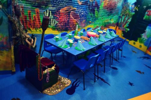 Fotografia przedstawia stół urodzinowy wraz z zastawą przygotowany na przyjęcie urodzinowe w pokoju morskim w Family Park.